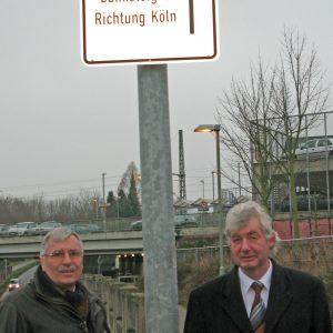 SPD-Ratsvertreter Volkmar Bromby und Hans-R. Müller am neuen Hinweisschild